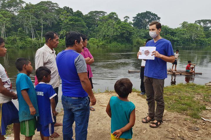 Mediziner Albanus erklärt Urarina-Indigenen, wie sie sich gegen das Virus schützen: