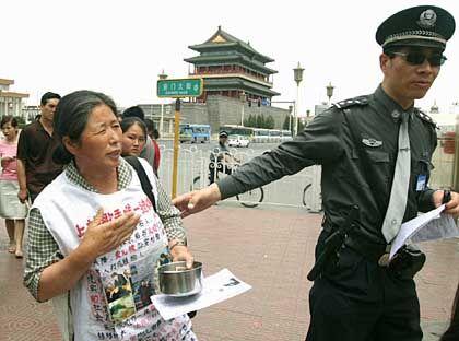 Demonstrantin, Polizist auf dem Tiananmen-Platz: Dissidenten und Angehörige von Opfern dürfen ihre Wohnungen nicht verlassen
