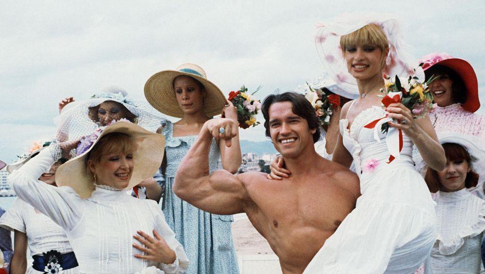 """Arnold Schwarzenegger 1977 am Strand von Cannes - als Werbung für seinen Film """"Pumping Iron"""""""