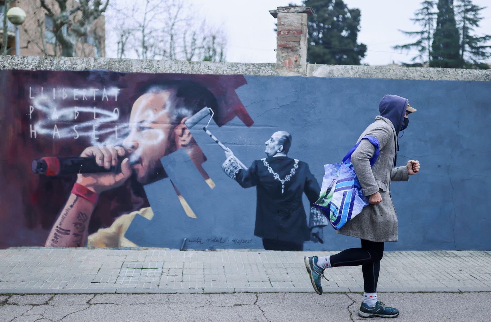 A person walks past a graffiti by Catalan artist Cinta Vidal in Cardedeu