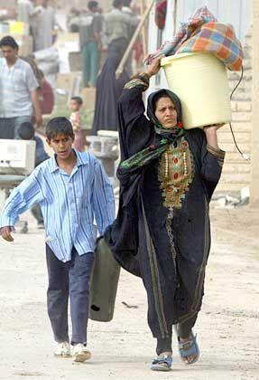 Fette Beute: Eine irakische Frau und ihr Sohn räumen ein Regierungsgebäude aus