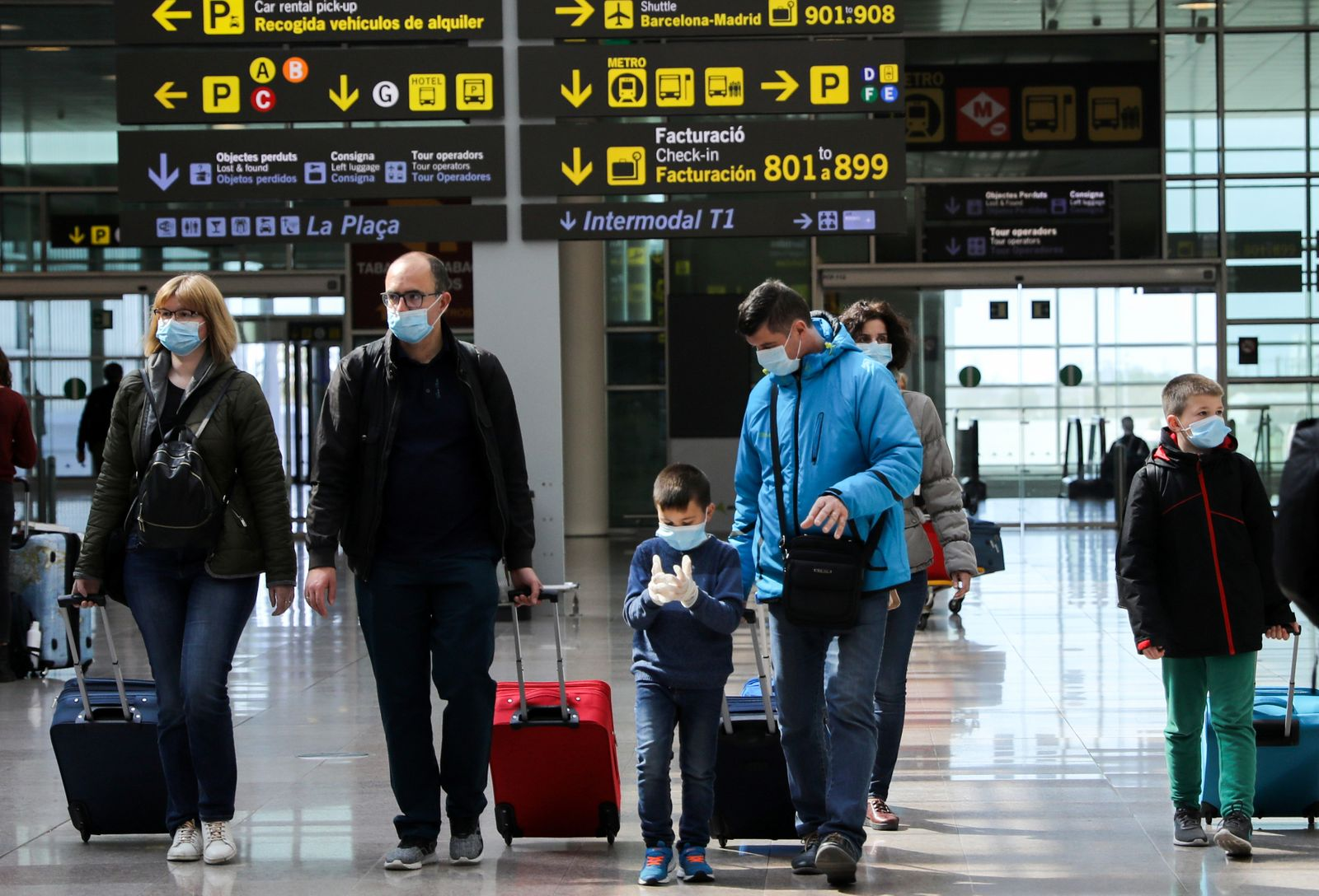 Families wear protective face masks as they walk with their luggage at Tarradellas Barcelona-El Prat Airport, after further cases of coronavirus were confirmed in Barcelona