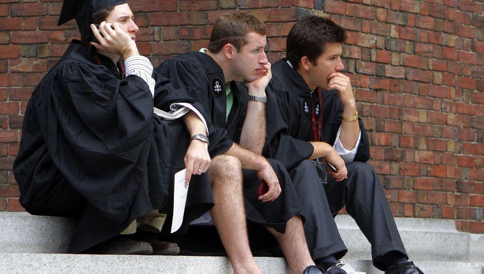 Graduierte der Harvard University sitzen auf Treppenstufen auf dem Campus
