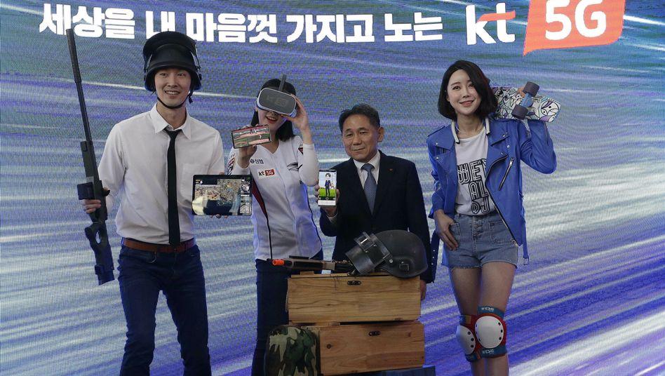 Ein Manager des Mobilfunkanbieters KT Corp. mit Models bei einer Feier zum Start von 5G in Südkorea