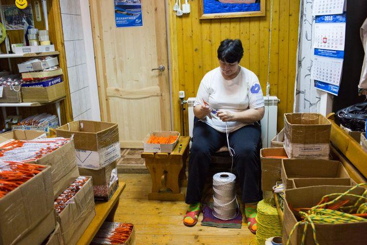 Eine Arbeiterin bereitet die Iglistchka, auf Deutsch Netznadel, vor, wickelt Nylonseile auf.