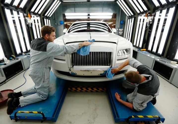 Alles muss glänzen: Zwei Arbeiter polieren einen Rolls-Royce
