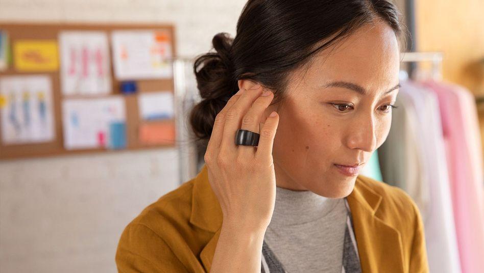 Diese Frau will sich nicht am Ohr kratzen, sie telefoniert gerade mit Amazons Smart-Ring Echo Loop