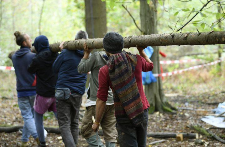 Aktivisten tragen im Hambacher Forst einen Baumstamm