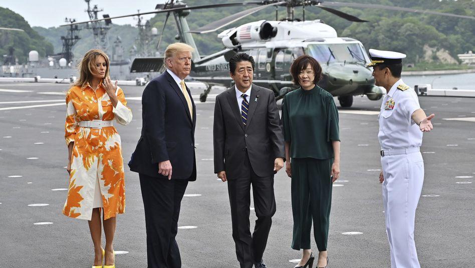 """US-Präsident Donald Trump (2.v.l.), Japans Ministerpräsident Shinzo Abe (M.), flankiert von First Lady Melania Trump (l.) und Akie Abe an Bord des japanischen Hubschrauberträgers JS """"Kaga"""""""