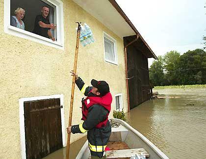 Ein Feuerwehrmann reicht den Bewohnern eines überschwemmten Bauernhofes im österreichischen Bergham Mineralwasserflaschen