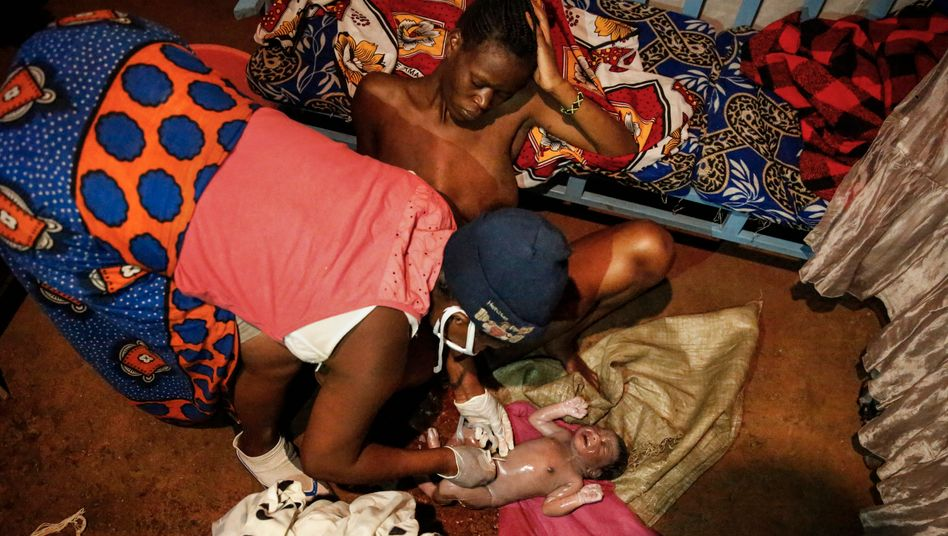 Midwife Emily Owino cuts the umbilical cord of a newborn girl with a razor blade in Kenya.