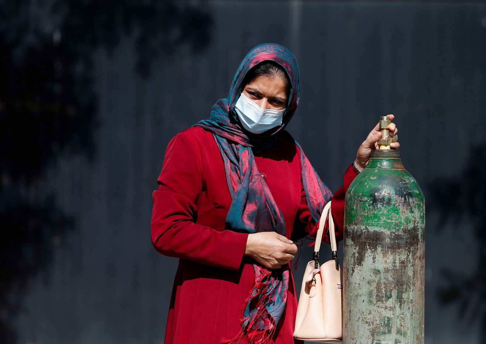 A woman waits outside a factory to get her oxygen cylinder refilled, amidst the spread of the coronavirus disease (COVID-19) in Kabul