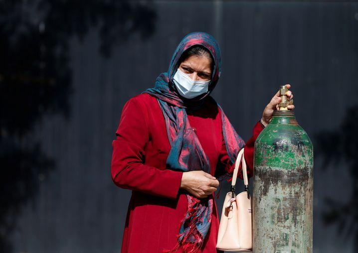 Eine Frau wartet vor einem Kabuler Krankenhaus auf Sauerstoffnachschub