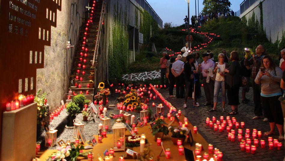 Kerzen brennen in Duisburg an der Unglücksstelle der Loveparade 2010