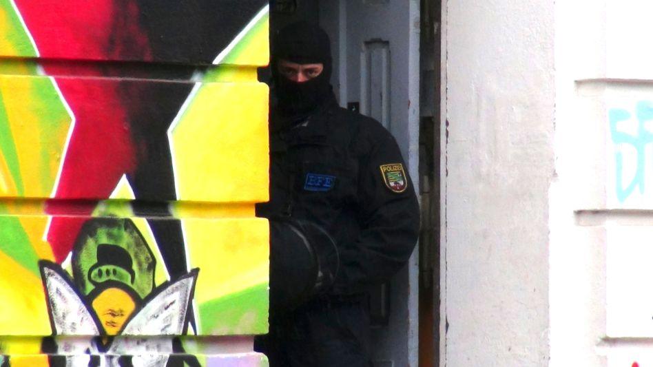 """Polizisten durchsuchen 2013 im Zuge eines Ermittlungsverfahrens gegen die """"Revolutionären Aktionszellen"""" ein Haus in Magdeburg"""