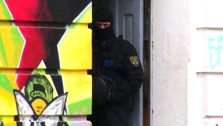 """Maskierte Polizisten durchsuchen im Mai 2013 im Zuge eine Ermittlungsverfahren gegen die """"Revolutionären Aktionszellen"""" ein Haus in Magdeburg"""