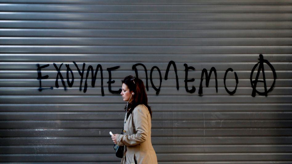 """A woman in Athens walking by a slogan reading """"We Are at War."""""""