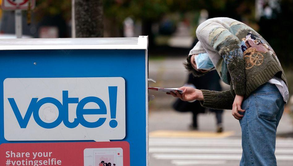 Ein Wähler in Seattle wirft seinen Stimmzettel in eine Wahlurne