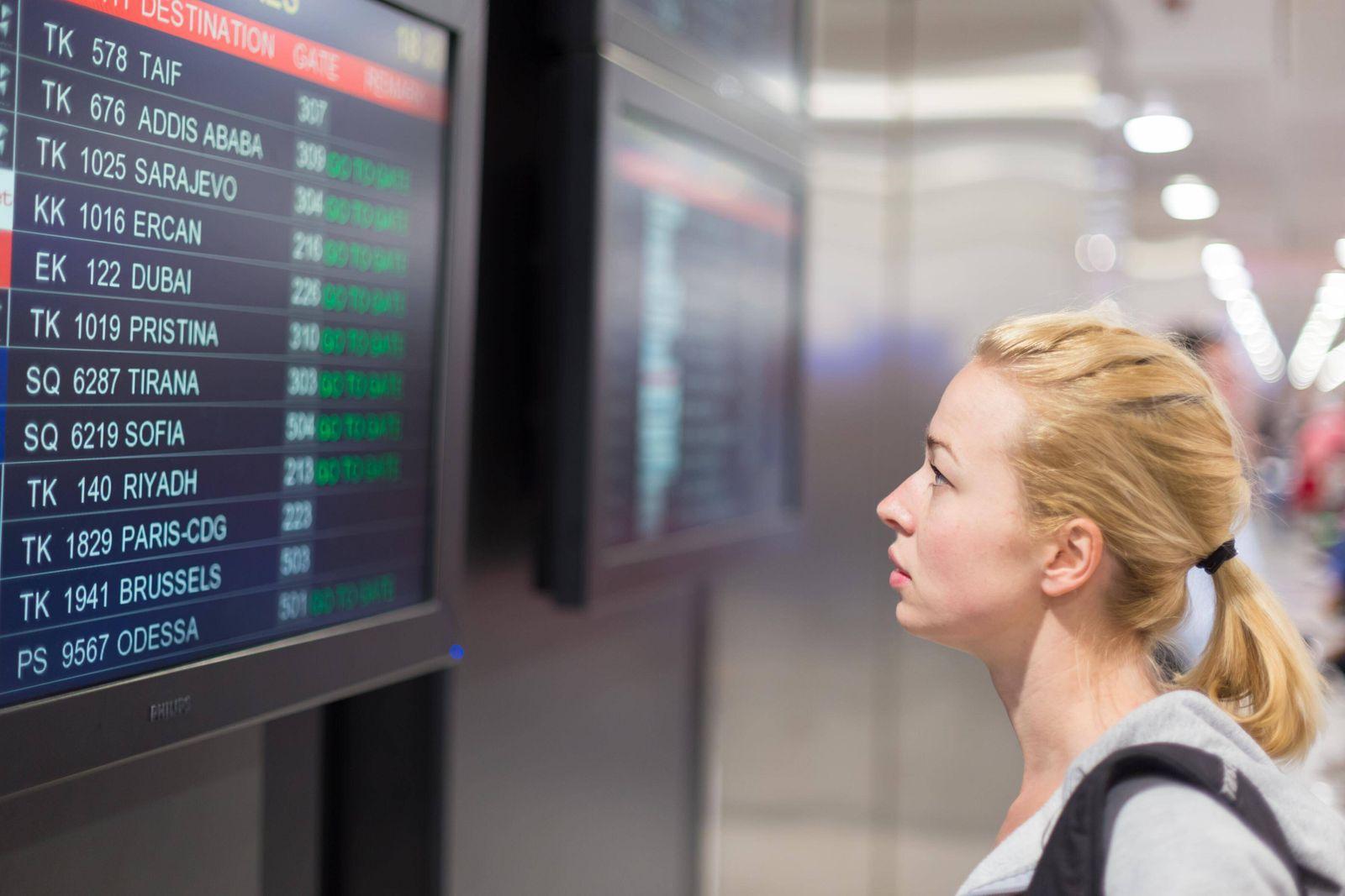 Passenger looking at flight information board model released Symbolfoto PUBLICATIONxINxGERxSUIxA