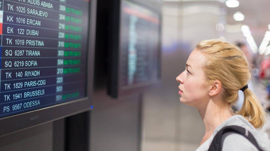 """Passagierin an einer Anzeigetafel für Flüge (Symbolbild): """"Auch kerngesunde Unternehmen halten das nicht länger aus"""""""