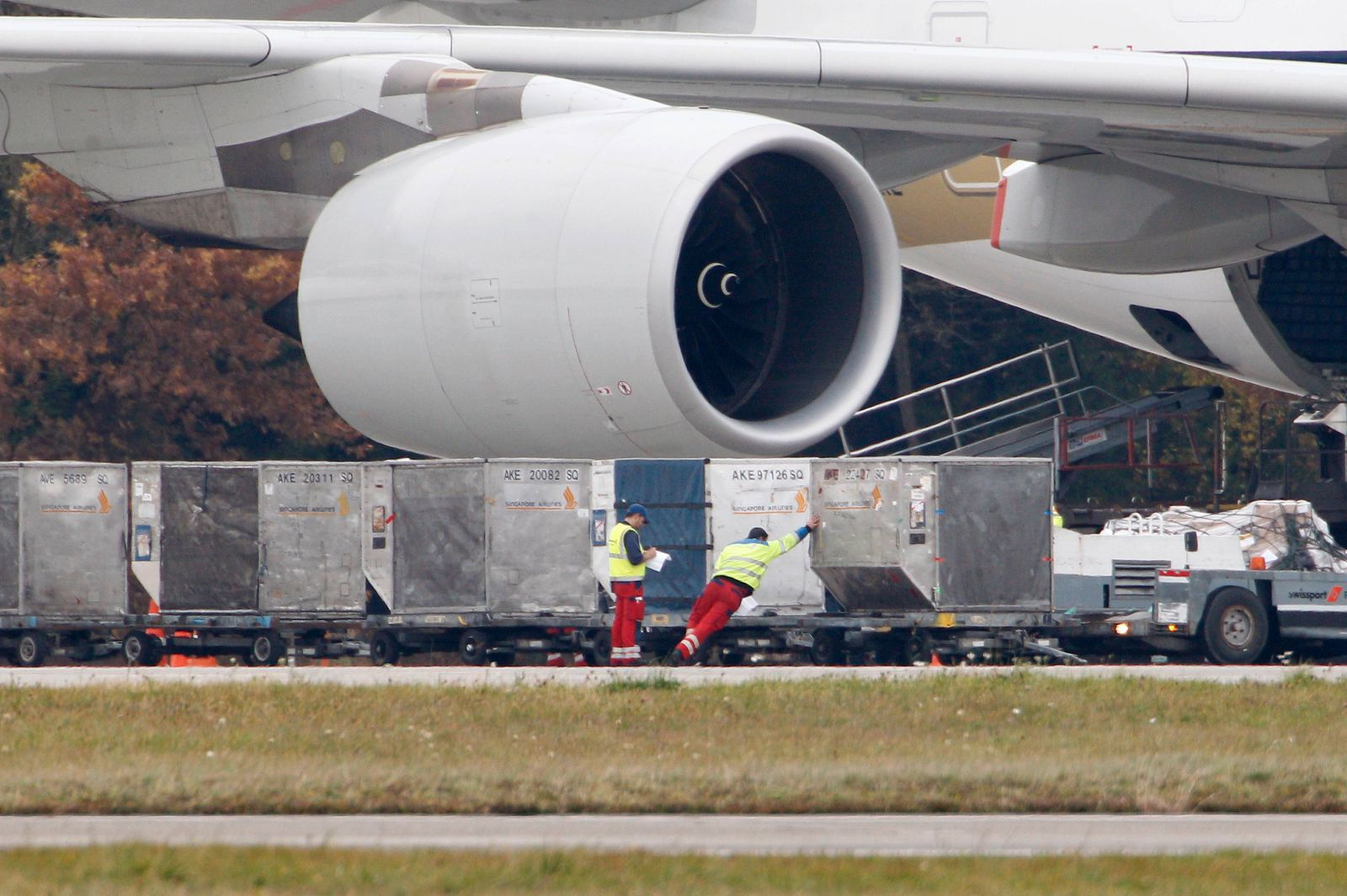 Ground crew members check freight containers to be loaded into a Singapore Airlines Airbus A380 superjumbo at Zurich Airport