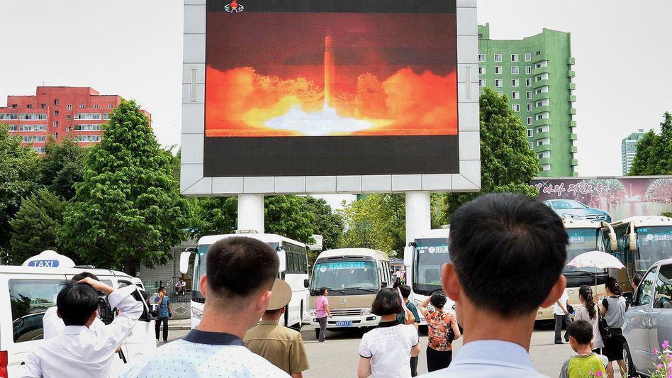 Passanten in Pjöngjang betrachten die Übertragung des jüngsten Raketentests