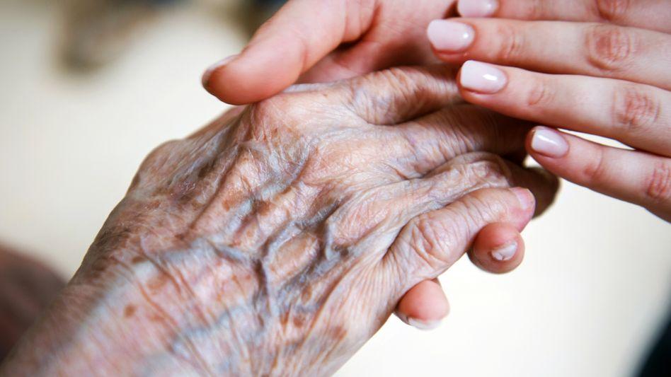 """Pflegerin hält die Hand einer alten Frau: """"Beschäftigungsverhältnisse wie in der Fleischindustrie"""""""