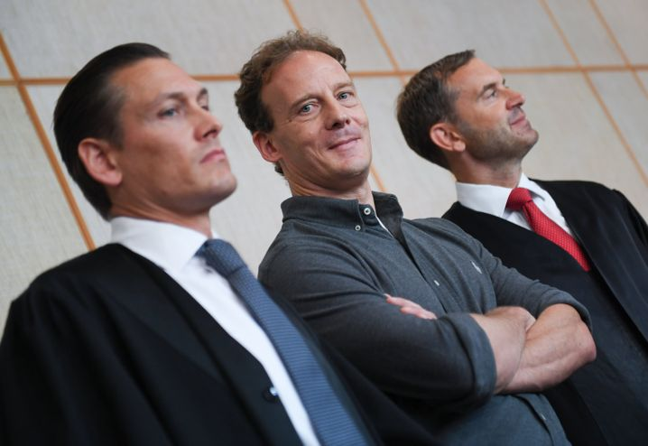 Der Angeklagte Alexander Falk (Mitte) wartet zusammen mit seinen Verteidigern Daniel Wölky (links) und Björn Gercke auf den Beginn des Prozesses