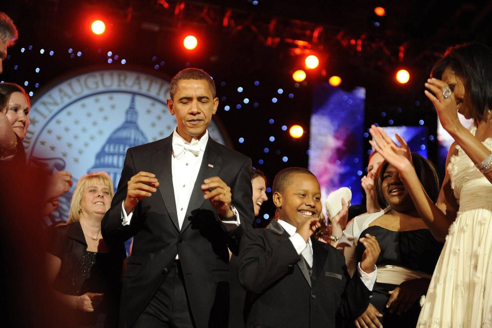 President and Michelle Obama dance with guests at the Neighborhood Ball. Michelle is wearing an ivory chiffon one should