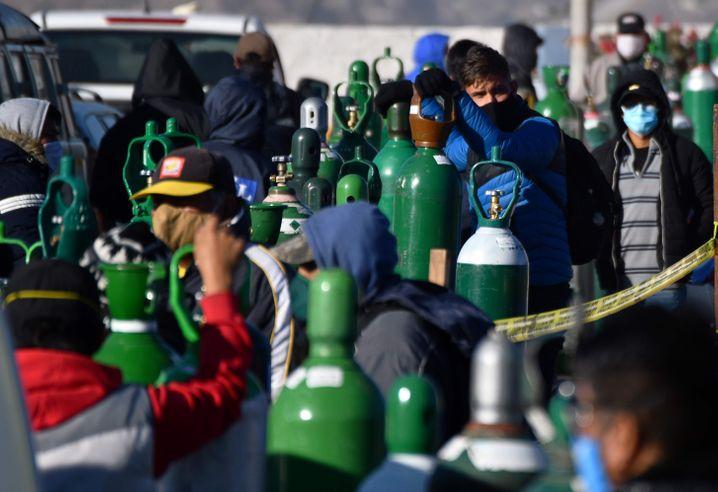 Warten auf den überlebenswichtigen Sauerstoff: Angehörige von Corona-Patienten warten mit leeren Flaschen auf frischen Sauerstoff