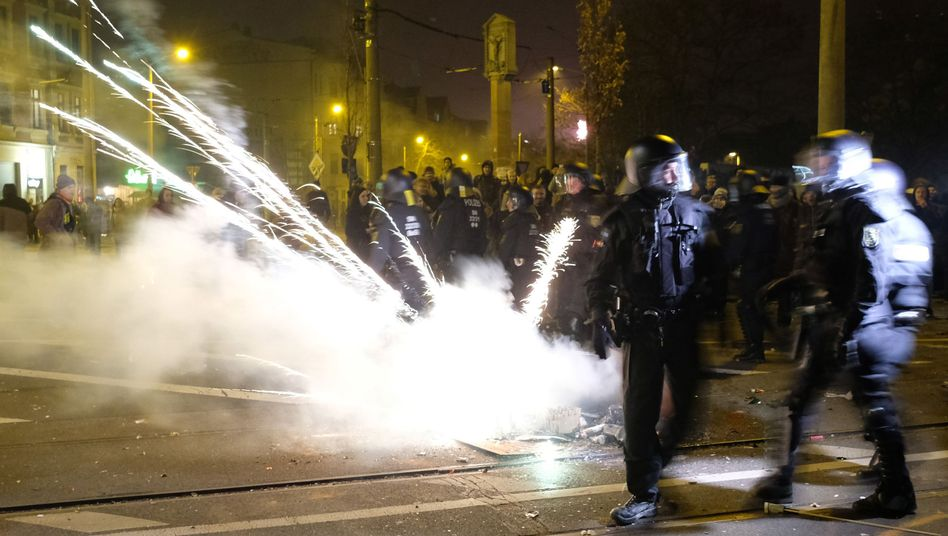 Polizisten räumen in der Silvesternacht eine Kreuzung im Stadtteil Connewitz