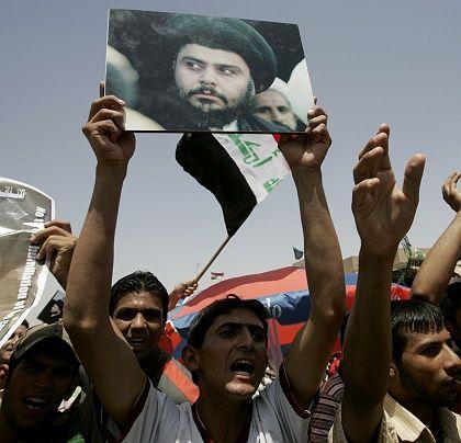 Demonstrators display a poster of anti-US cleric Muqtada al-Sadr in Baghdad.