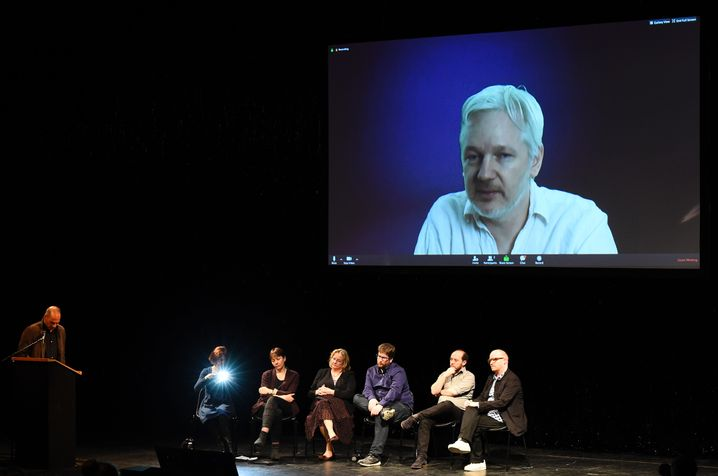Varoufakis mit Gästen in der Berliner Volksbühne, auf der Leinwand Assange