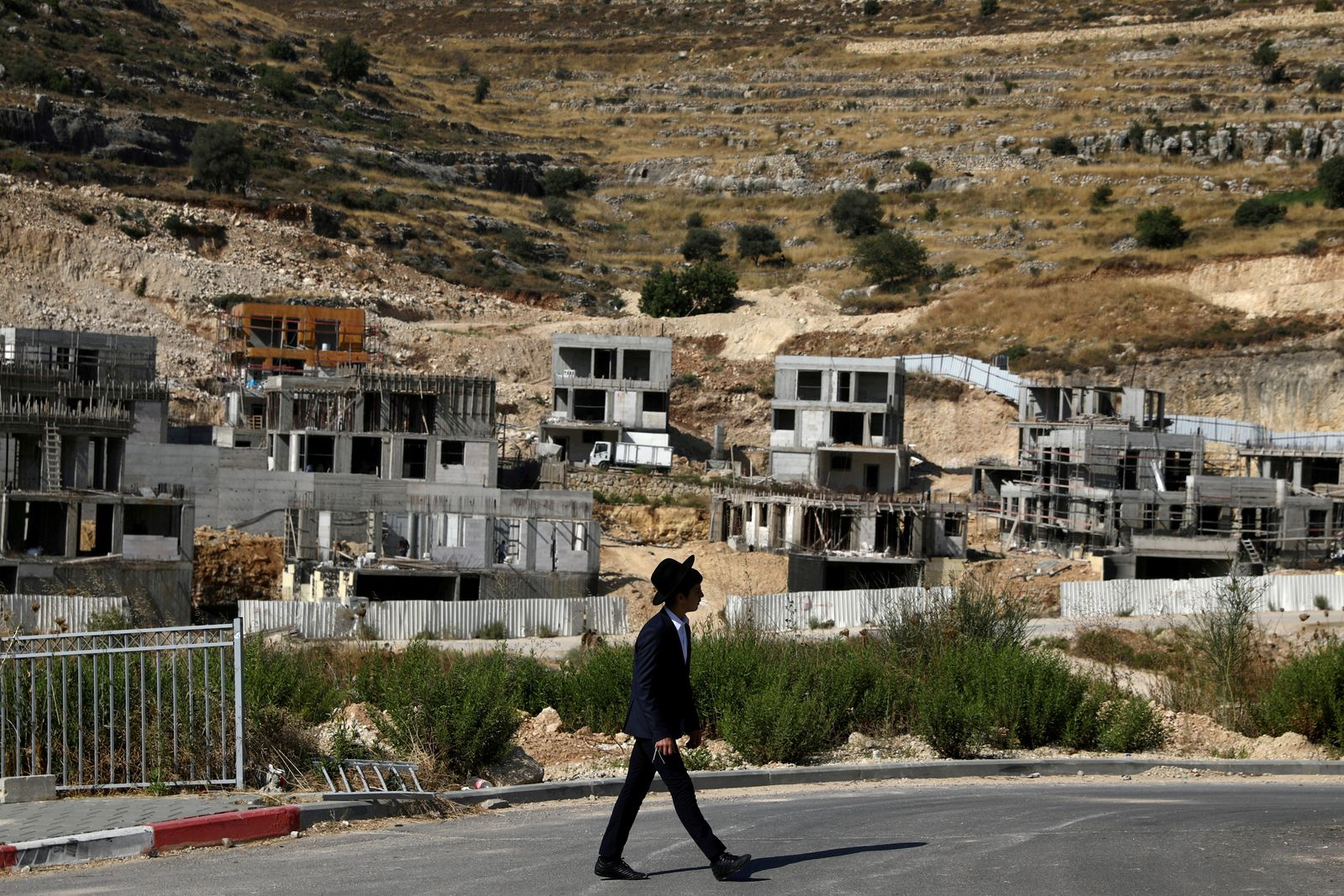 FILE PHOTO: A Jewish settler walks past Israeli settlement construction sites around Givat Zeev and Ramat Givat Zeev in the Israeli-occupied West Bank