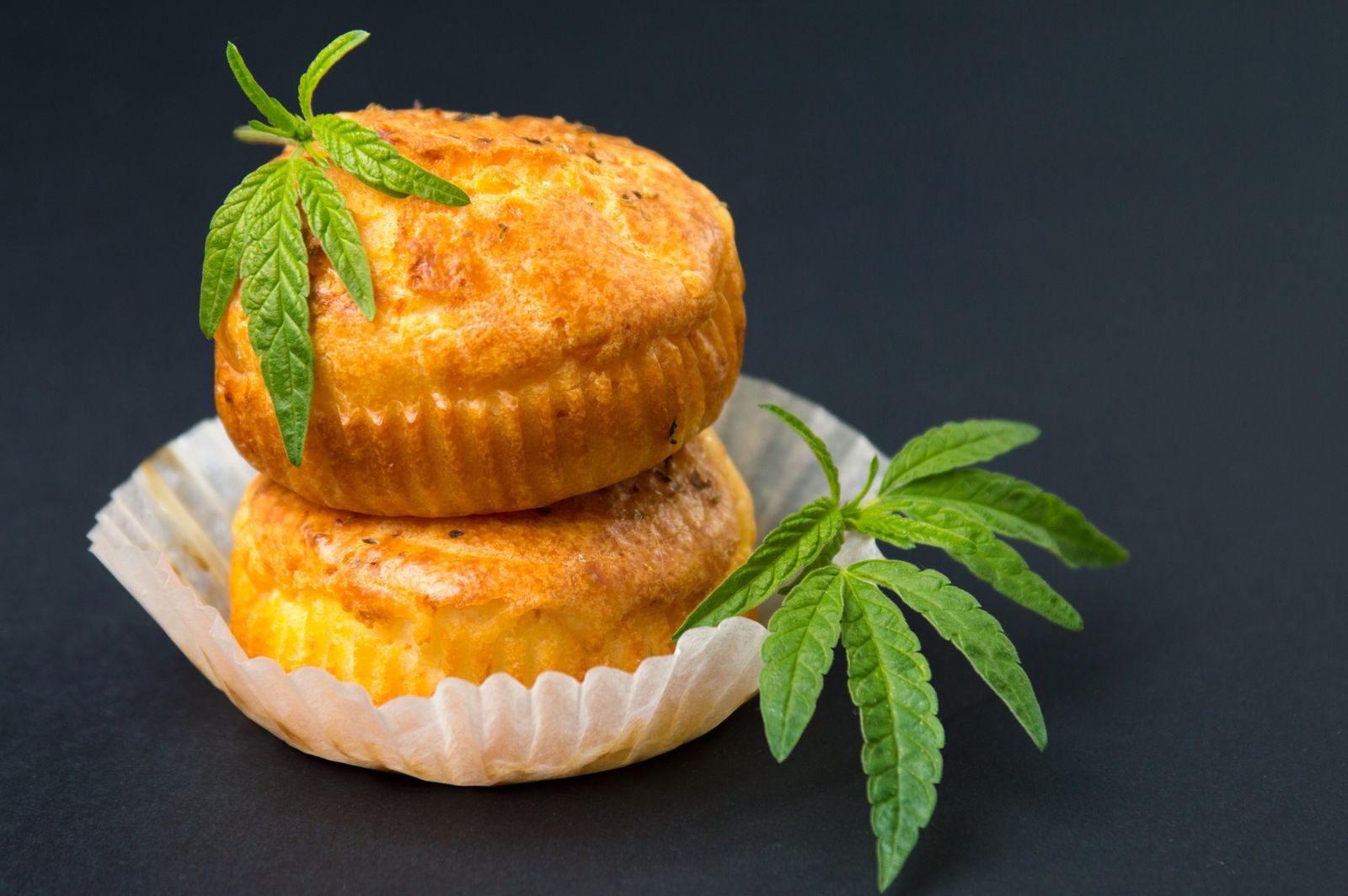 Cannabis cupcake muffins and leaves in paper cups (CreativeFamily)