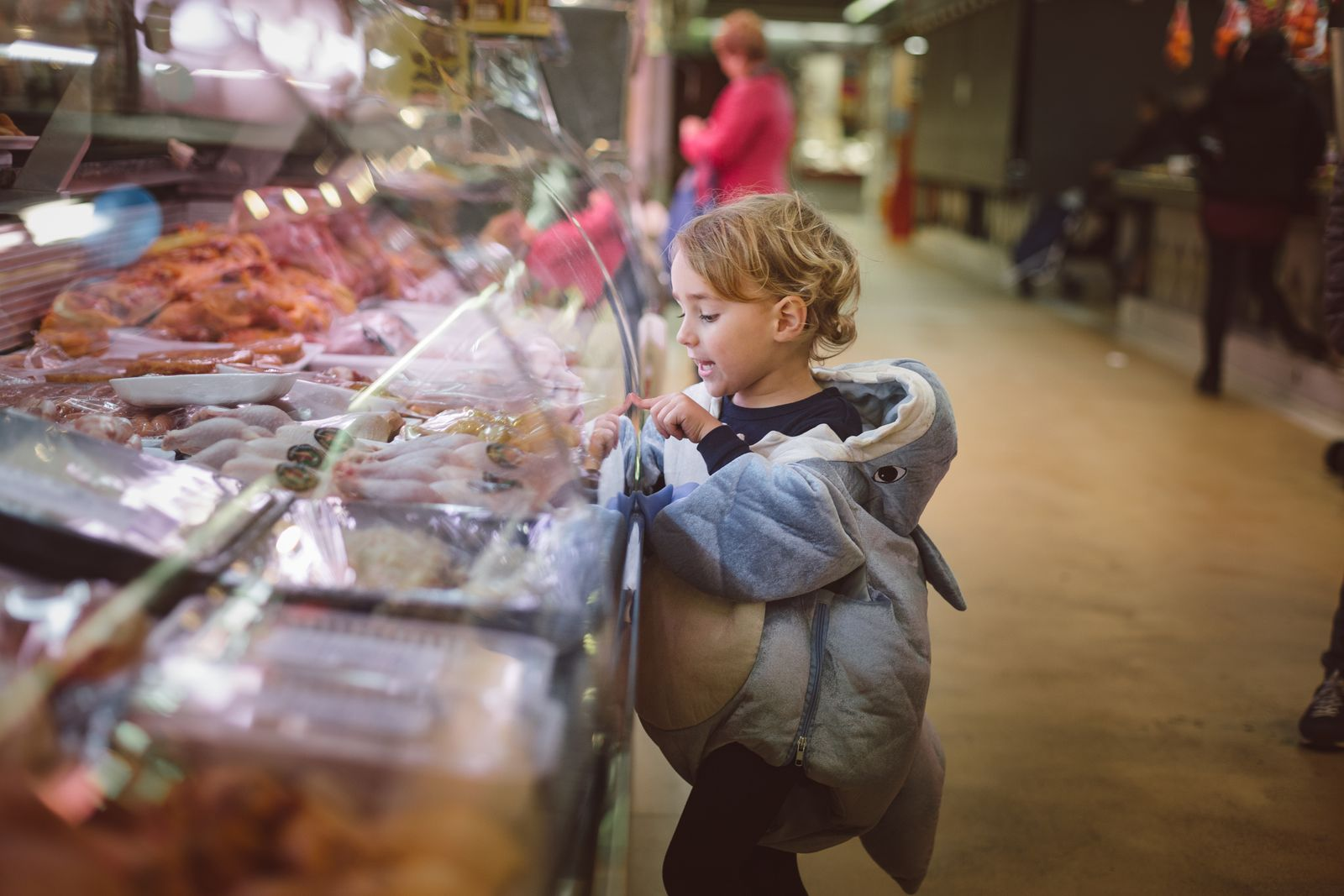 Boy dressed as a shark looking at the meat in the market