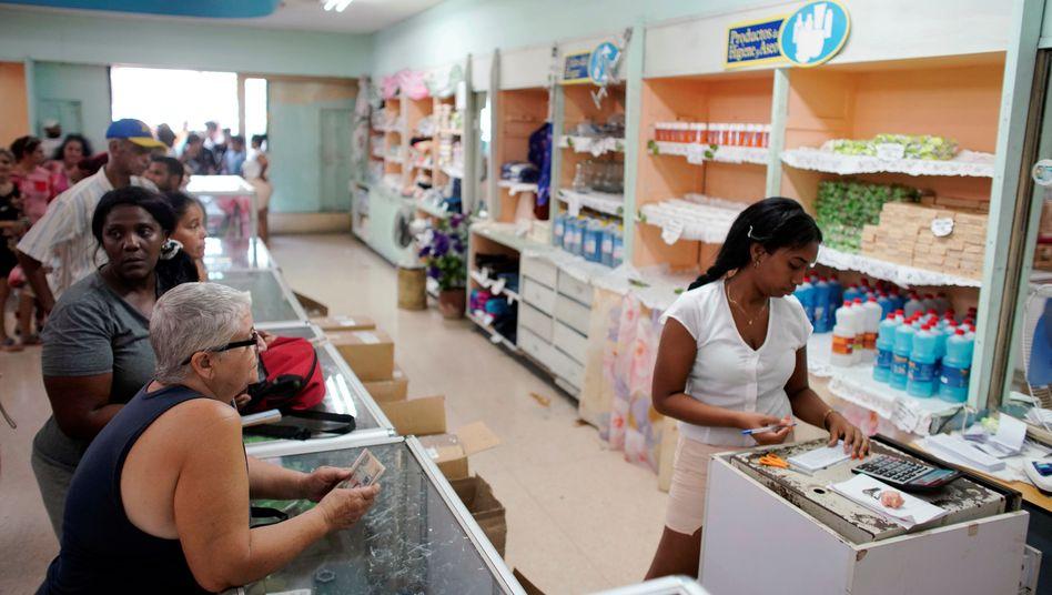 """Kunden, Verkäuferin in staatseigenem Laden in Kuba: Gekauft werden darf nur noch in begrenzter Menge - laut Regierung für eine """"gerechte und vernünftige"""" Verteilung"""