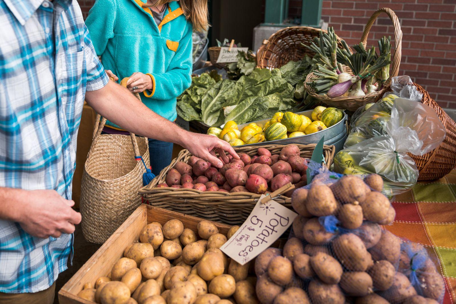 Man and woman gather potatoes at farmers market Port Angeles, WA, United States PUBLICATIONxINxGERxSUIxAUTxONLY CR_ADMC