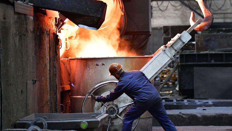 Volle Kraft für die Wirtschaft: Ein Beschäftigter arbeitet in einer Eisenguss-Werkhalle.