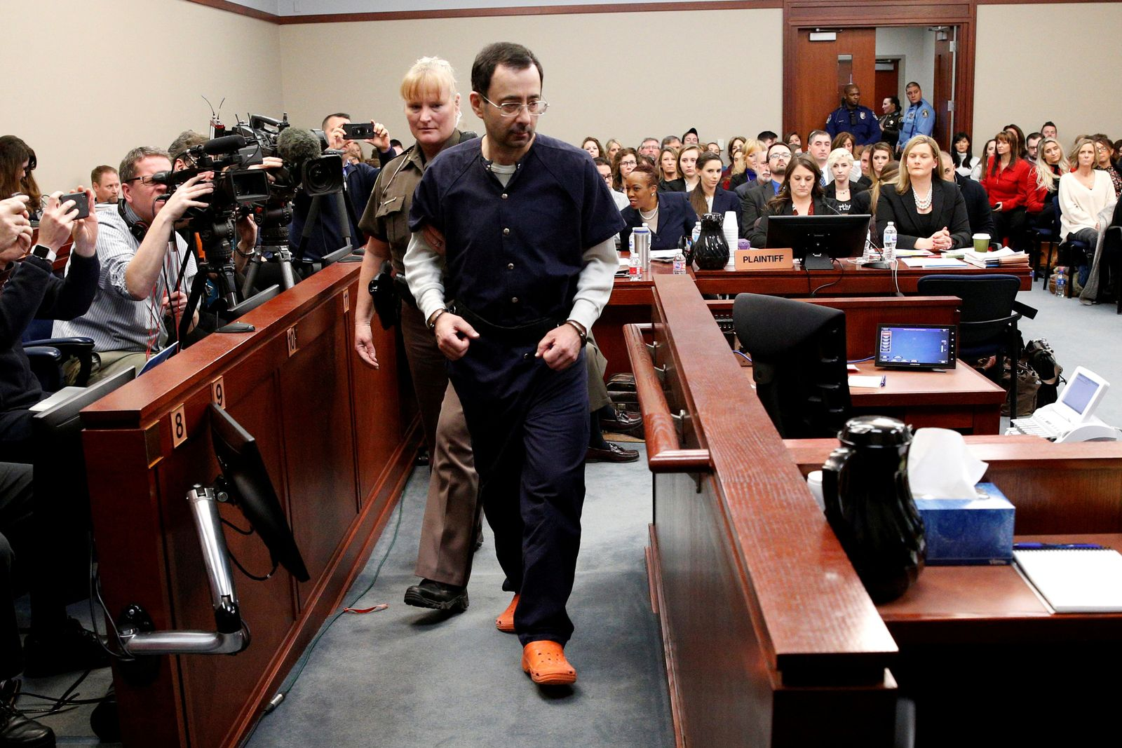 FILE PHOTO: Larry Nassar, a former team USA Gymnastics doctor who pleaded guilty in November 2017 to sexual assault charges, is escorted into the courtroom during his sentencing hearing in Lansing