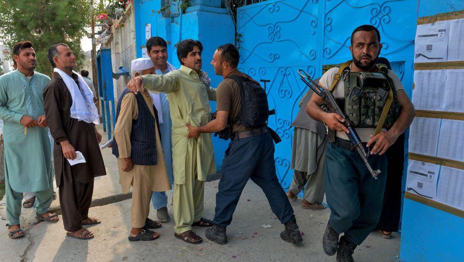 Afghanische Beamte bei einem Sicherheitscheck von Wählern vor einem Wahllokal in Jalalabad