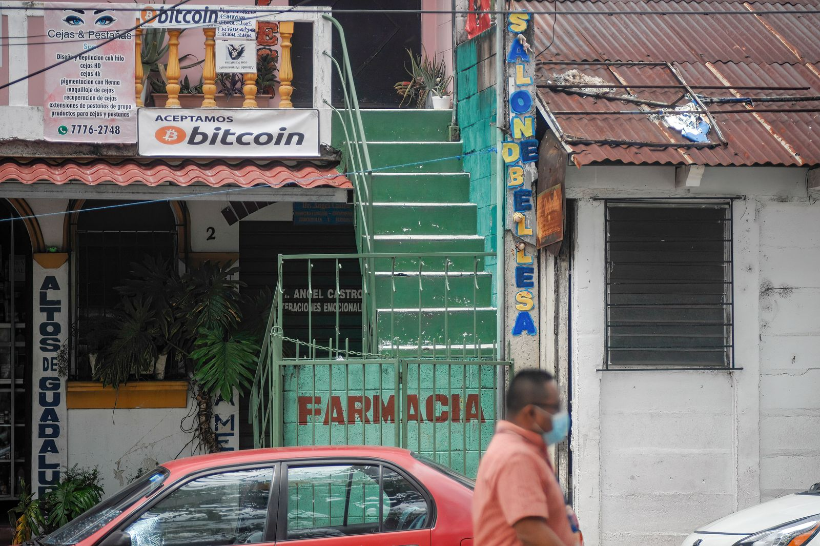 A man passes by a local business that accepts bitcoin as a