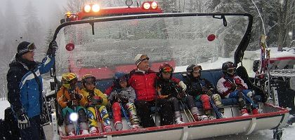 Then Russian President Vladimir Putin (center) sits together with children from a local sport school as they wait to be lifted up the mountain in Sochi in 2007.