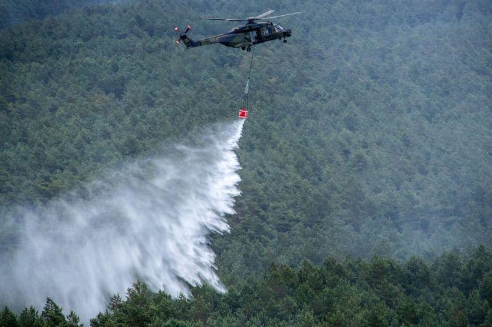 Waldbrand in Mecklenburg-Vorpommern: Ein Hubschrauber der Bundeswehr vom Typ NH90 wirft in der Nähe von Alt Jabel über einer Brandstelle Löschwasser ab