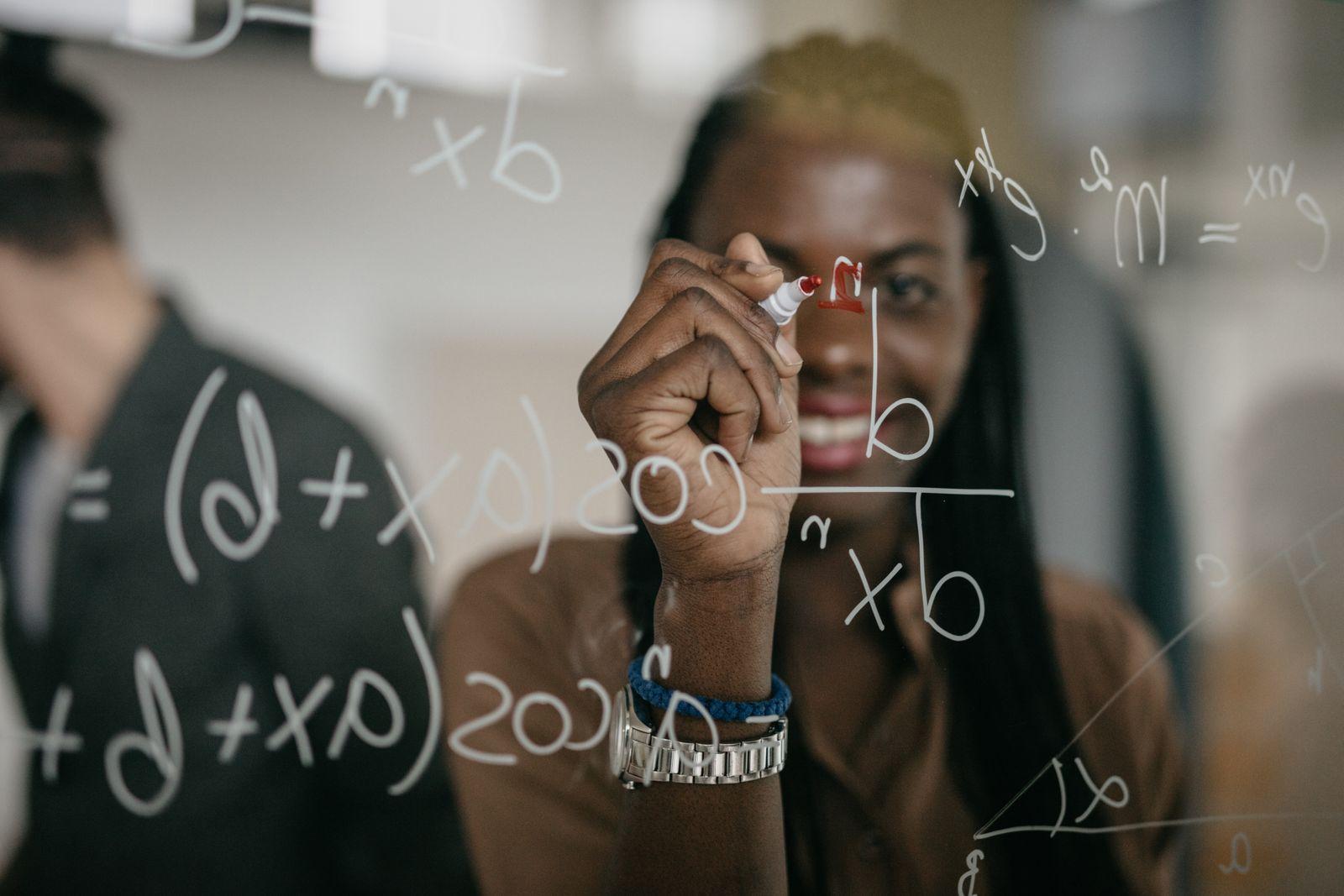 Professor Writing Mathematical Formulas on a glass