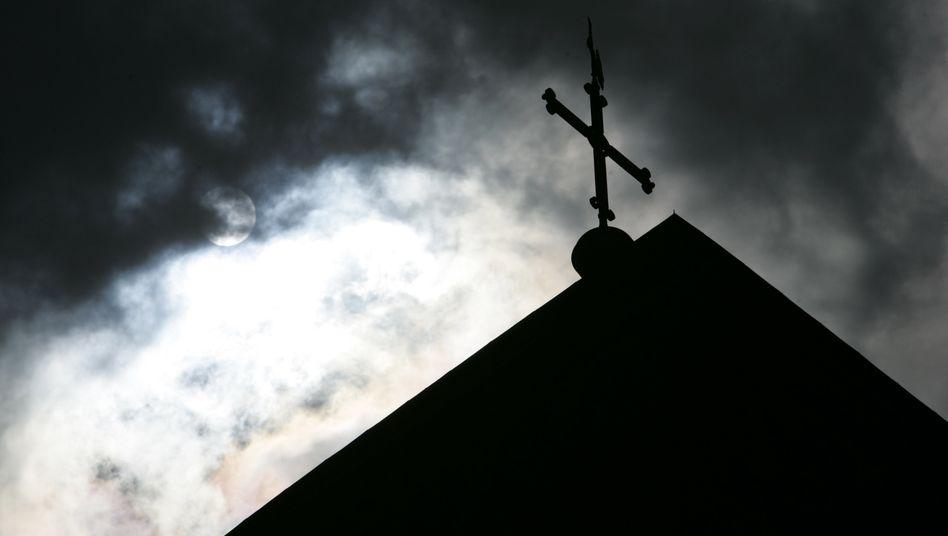 Kirchturmspitze mit Kreuz: Düstere Zeiten in der katholischen Kirche