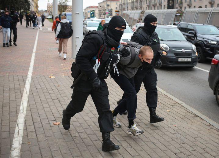 Polizisten nehmen einen Demonstranten fest
