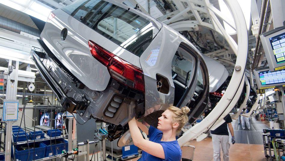 VW-Werk in Wolfsburg: Eine Mitarbeiterin schraubt am neuen Golf 8