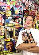 Titanic's editor Martin Sonneborn poses by a wall displaying Titanic covers over the years.