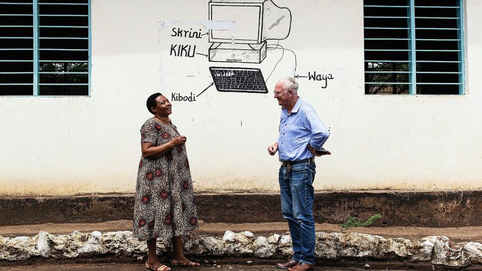 Teacher Godfrey and journalist Grill in front of the school in Longido, Tanzania: For the students here, computers exist only as drawings.